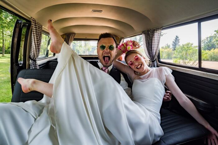 Les mariés s'amusent comme des fous sur notre banquette arrière pour un cortège vintage